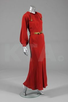 A burnt orange crepe evening gown, possibly a copy of a Schiaparelli, late 1930s, with gilt cords and baubles to the neck, similarly adorned belt, and bias cut with full sleeves.