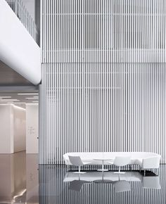 A screen of spray-painted extruded aluminum slats dominates a lobby at Maike Group in Xi'an, China. Most of the complex was a collaboration between Hallucinate Design Office and Interdesign Associates. Photography by Javier Callejas. Interior Design Magazine, Lobby Interior, Interior Architecture, Commercial Design, Commercial Interiors, Commodity Exchange, Office Lobby, Lobby Design, Atrium Design