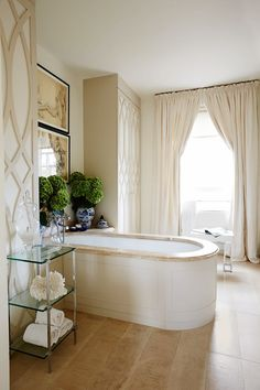 The bathroom in Lauren Gurvich King's Belgravia house has floor-to-ceiling cabinets with a decorative fretwork design backed with pale linen and a deep bath. The neutral palette creates a sense of calm, and allows the two reproduction Chinese urns, which are used as vases, to stand out. Lauren bought the glass étagère to the left of the bath from Paolo Moschino for Nicholas Haslam in south-west London.