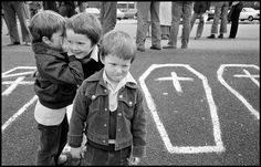 Ian Berry GB. NORTHERN IRELAND. Belfast. Small boys at a demonstration in support of H-Block hunger strikers with coffins painted on the pavement. 1981.