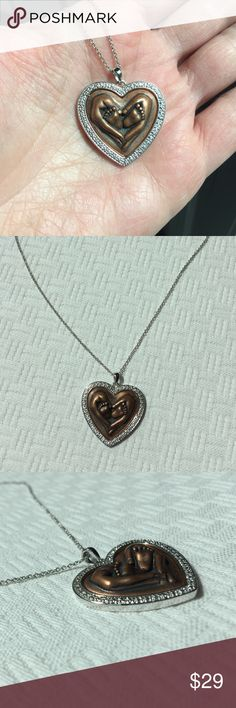 Mother's hands babies feet heart shaped necklace This beautiful little necklace is done in the look of copper with Silvertone border. The design is a mother's hands wrapped around babies feet. The necklace is Silvertone and measures 18 inches long with a spring ring clasp. Perfect for a new mom grandmom or godmother. I only have three of these gorgeous necklaces left.  gift box included. Jewelry Necklaces