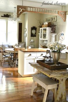 Faded Charm: Old porch trim hung from ceiling separates kitchen and dining areas.
