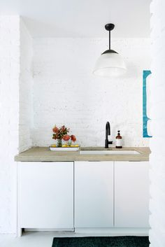 concrete countertops and painted white brick walls in minimalist kitchen restored by the fords. / sfgirlbybay