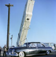 March 23, 1962 President John F. Kennedy's bubble-top limousine drives away from Minuteman missile silo. Silo-lift launcher is visible in background. Vandenberg Air Force Base, California. - John F. Kennedy Presidential Library & Museum