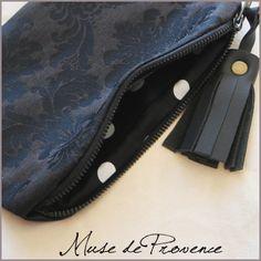 Petit sac pochette de soirée TOUT NOIR   Muse de Provence.   Petit sac pochette de soirée. A porter à la main ou à glisser dans le cabas.  Face 1: en tissu damassé noir  Face 2: en tissu satin de coton noir  Avec un pompon en cuir noir H8cm. Intérieur doublé en tissu. Double face.  Fermeture par zip.  Dimensions: H15cm L22cm