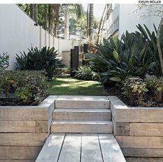 Para conter o desnível, o paisagista Luiz Felipe Rudge Leite preferiu a madeira ao muro de arrimo convencional. Assim, degraus e prancha de acesso ao jardim têm unidade visual.