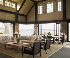 Beautiful waterfront cottage living room with exposed wooden beams, taupe walls, neutral furniture, stone pillars and grasscloth on the ceilings Living Room Lounge, Living Spaces, Living Rooms, Mountain Dream Homes, Taupe Walls, Paint Colors For Living Room, Coastal Living, Cottage Living, House Layouts