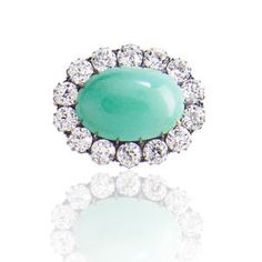 An antique turquoise and diamond brooch, circa 1840 centering an oval turquoise cabochon, within an old European-cut diamond surround; estimated total diamond weight: 10.00 carats; mounted in silver and fourteen karat gold.