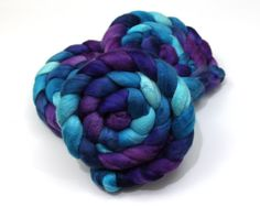 Merino Wool/ Yak/ Silk Roving (60/20/20) (Combed Top) - Hand Painted Spinning Fiber - 4 oz.  Colors in this roving include turquoise, navy, sky blue, violet, and plum.  This luxurious blend of Merino wool, Yak fiber, and cultivated silk is wonderfully soft.  Blend: 60% Merino Wool 20% Yak Fiber 20% Cultivated Silk  * Our fibers are dyed by hand with colorfast commercial dyes for a one-of-a-kind appearance. Be aware that colors may appear differently on different computer monitors, but every…