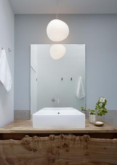 """The Gregg Pendant Light from Fosacari is an alabaster-like soap bubble that seems to float out of the skylight. Its irregular form loosens up the room. The sink is a deck-mounted Aquagrande Wash Basin from Lacava and the mirror-mounted Vola In-Wall Mixer Faucet was designed by Arne Jacobsen.""Jerome Buttrick bathroom, via Remodelista"