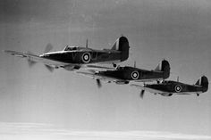 """A formation of No 85 Squadron RAF from RAF Church Fenton executes a balbo on 5 October 1940, for the benefit of AM photographer Bertrand JH Daventry, who flew in a Master Mk I of No 306 Squadron RAF to undertake the photography. Among the 12 aircraft taking part in the display S/L Peter W Townsend led the front echelon in Hurricane Mk I VY-U, with acting F/L Geoffrey """"Sammy"""" Allard of A Flight abaft in VY-G and acting F/L James E """"Nigger"""" Marshall of B Flight to the rear in VY-Q."""