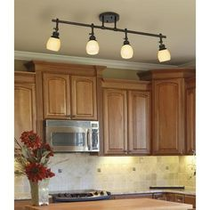 Replace fluorescent light in kitchen with track lighting and add small lights under the cabinets.
