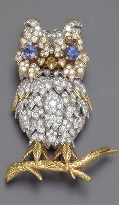 A DIAMIOND AND SAPPHIRE BROOCH  Designed as an owl, accented by circular-cut diamonds, with circular-cut sapphire eyes, sitting atop a textured gold branch, mounted in platinum and gold