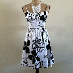 Dress Beautiful white dress w black flower pattern. Adjustable straps and zip closure in back. Sash that ties in back. Worn once for a wedding, perfect condition. Dresses