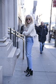 Brooke Testoni wears Zimmerman Mischief Rosette Blouse, high-waisted denim jeans and black, heeled ankle boots.