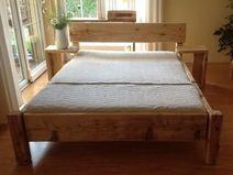 Bett aus Dielen mit Beistelltischen