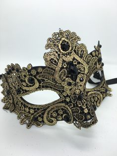 Black and gold Mardi Gras mask with lace, black stones and ribbon ties.