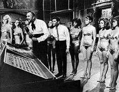 Actors Vincent Price (left) and Dwayne Hickman are surrounded in a lab by unidentified actresses in bikinis in a still from the film 'Dr. Goldfoot and the Bikini Machine,' directed by Norman Taurog, San Francisco, California, 1965