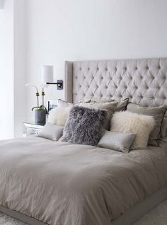 taupe colored upholstered bed with taupe pillows looks very inviting yet neutral