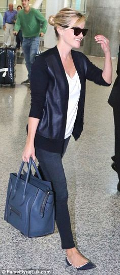 Simply chic: For her flight, Reese wore a pair of washed out black jeans with a simple white T-shirt and a stylish leather paneled cardigan