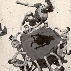 Teenaged boys using blanket to toss their friend, Norma Baker, into the air on the beach. These photographs were taken by LIFE photographer John Florea at Hermosa Beach, CA, US. July 1948