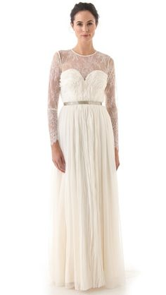 Catherine Deane Madonna Long Gown Sheer lace is an ethereal, delicate accent on a beautiful gown from Catherine Deane. Composed of chiffon pleats with frayed, feathered edges, this long dress has a boned bodice with an illusion sweetheart neckline and a bright beaded band that encircles the waist. The back closes with a hidden zip, and the hem falls to a floor-skimming length with a slight train. Fitted, sheer lace sleeves provide an elegant finish. Fully lined in silk charmeuse.