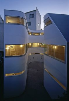 """Residential Architecture: NE Apartment Residence by Nakae Architects: """"..'NE apartment' is an 8-unit apartment complex dedicated to motorcycle enthusiasts in tokyo, japan by japanese firmnakae architects.the building's square footprint features a C-shaped outdoor area which is carved from the interior and accessed from a private alleywhich leads to the street. borders a centralized communal area, the curved facade allows enough length for access into each unit'sbuilt-in garage while dwellers"""