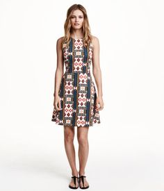Short sleeveless dress in jersey with a seam at the waist, racer back and bell-shaped skirt.