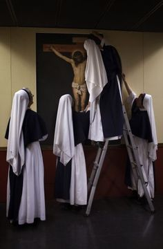 The Sisters of Life fix a poster with the image of Jesus Christ after hanging it on the wall of an improvised chapel at a sports stadium in Madrid Monday Aug. 15, 2011. (Creative Minority Report) (AP Photo/Emilio Morenatti)