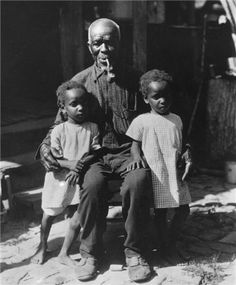 CUDJO LEWIS (1841-1935)  was the last survivor of the Clotilda, the last ship to illegally transport captive Africans (members of the Tarkbar tribe, had been captured by the Dohomey tribe during the tribal warfare in Ghana at the time), to the US.  Among those Africans was a man named Cudjoe Lewis (Kazoola); the last surviving member of the original Africans.  |  Cudjo embraces his twin granddaughters, Martha and Mary West (age 4), in Africatown.  Univ. of South Alabama Archives (c.1930).