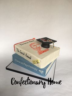 Stack of text books cake for this chid psychiatry graduate. The book are layers of cake covered in fondant, hand painted, and topped with a fondant graduation cap.