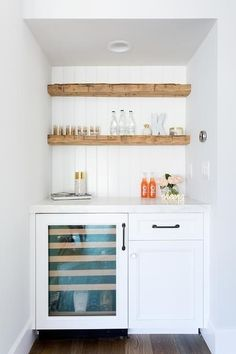 Rustic floating bar shelves are mounted against a white beadboard trim above a glass front mini wine fridge fixed beside white cabinets donning oil rubbed bronze pulls and beneath a white marble countertop. Bar Shelves, Wood Shelves, Glass Shelves, Floating Shelves, Corner Shelving, Shelf Desk, Rustic Shelves, Open Shelving, Kitchen Wet Bar