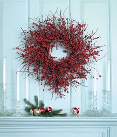A circle of winterberry branches brightens a mantel scene. Instructions: Cut 40 to 50 branches of winterberries to measure between 10 and 16 inches long. Using green florist wire, attach the larger branches to a 16- to 18-inch wire frame one at a time, overlapping as you go. Continue adding smaller branches until it looks full; use a glue gun when the wiring becomes too difficult.  - GoodHousekeeping.com