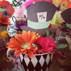 Mad Hatter Tea Party Centerpiece. Tea cups from around the house, dollar tree flowers and green foam. Mad hats and construction paper flowers (on toothpicks) stuck in foam as well. So easy and inexpensive but a big impact paired with some books and Chinese lanterns for an Alice and Wonderland birthday.