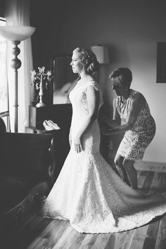 Mother of the Bride buttons up the wedding dress on wedding day / Lace bridal gown / LEB is weekend wedding destination & barn event venue located in the Texas Hill Country / Photo: J. Violet Photography