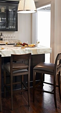Accommodating transitional style. Our exclusive Dixon Bar Stool complements any space, with a simple paneled back and tapered legs that call attention to the Hemingway leather upholstery and solid-mahogany construction.