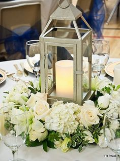 This would be a great option to consider: one main candle with surrounding flowers instead of center vase with surrounding flowers (simple diy wedding reception) Lantern Centerpieces, Wedding Reception Centerpieces, Wedding Lanterns, Reception Decorations, Wedding Table, Centrepieces, Centerpiece Ideas, Diy Wedding, Wedding Ceremony