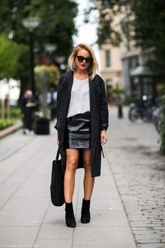 Stockholm Streetstyle. Long Coat/Sweater over tee + leather mini + ankle boots. Black and White.