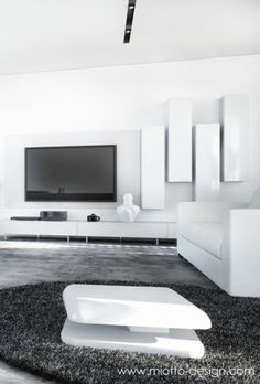 Modern black and white living room with a white leather sofa, white coffee table and white wall cabinets. A big TV in the middle of the the wall.