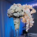 White phalaenopsis orchids drape over the side of a glass centerpiece full of white peonies and hydrangeas.