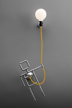 One and only, designer wall lamp with single light globe. A pipe guy with a balloon. Here shown in a very joyful color combination - warm, nickel metal finish and yellow braided cord. Artful statement piece for any modern or loft spaces.