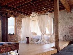 love the wall behind the bed as well as the stunning white drapes.... nice idea to raise the 'bed' part of a loft room too