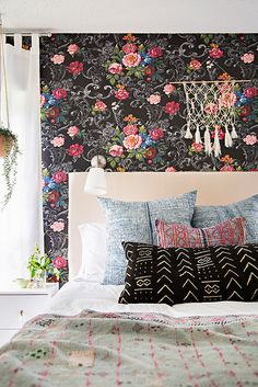 Super adorable girly bedroom with floral wall paper, hanging plants, and printed pillows