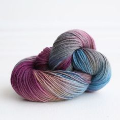 Three Irish Girls Yarn Inc.'s Meg, shown on Carys BFL.  Meg is a beautiful combination of plum, rosy mauve, and cornflower blues with dashes of pale grays and browns that flow in and out of each other creating a watercolor effect to the skein.  It carries an air of sophistication just like the accomplished Meg March.http://threeirishgirls.com/products/copy-of-new-doges-palace-1
