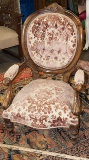 VICTORIAN PARLOR CHAIR. THIS ANTIQUE BEAUTY HAS A ROUND BACK WITH THE MOST BEAUTIFUL WOOD GRAIN. THERE ARE DELICATE CARVINGS THROUGHOUT AND A SCROLL FINIAL. SOFT PADDED BACK, ARMS AND SEAT TAKES YOU BACK IN TIME TO A VICTORIAN SITTING ROOM. MEASURES 40 INCHES HIGH, 27 INCHES WIDE AND 31 INCHES DEEP.