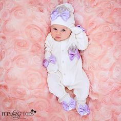4 piece set includes: onesie, mittens, cap, shoes. Embellished with bows, rhinestone buttons and jeweled crowns.  Each set has a set of jeweled angel wings on t