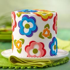 Make bold flower fondant cut outs and layer on a buttercream-iced cake to achieve this clean cake design. Learn how: http://s.wilton.com/1giGlXl #fondant #spring #cakedecorating