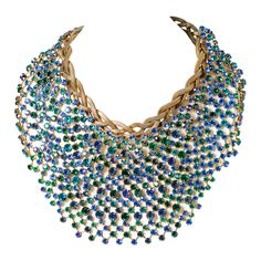 CIS Bib Necklace. Countess Cissy Zoltowsa, who design career began in 1951 hand painting cuff links. By the mid 1950s she started working for Pierre Balmain and Jacques Fath. She also worked for Balenciaga for 14 years. Her Jewelry was sold at Bonwit Teller under Countess Zoltowska and at Lord and Taylor under Cis of Paris. The Necklace is a large and bold piece, measuring 16 inches by 5 1/2 inches.  It consists of a mixture of Blue, Green and Blue-Green iridescent stones. The chain in ...