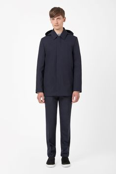 In crisp technical cotton, this clean, modern coat has a detachable hood and neat rounded collar. Designed for practical everyday wear, it is a straight shape with inside and outside pockets and a hidden zip fastening along the front.