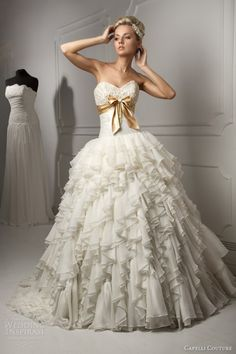 this beautiful gown is from Russia a Capelli couture ruffled wedding dress. highlighted by the gold bow.